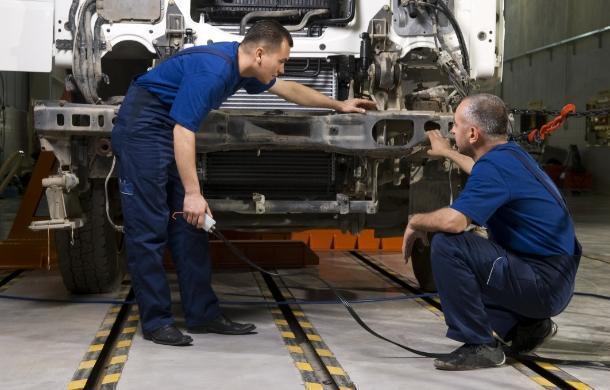 Dwóch mechaników przed rozkręconym tirem